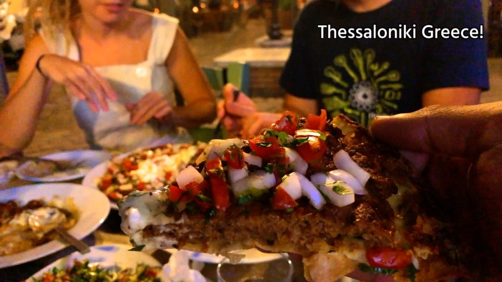 Don't miss the giaourtlou in Thessaloniki! A seasoned meat patty with tomatoes and onions on top of a thin dough crust