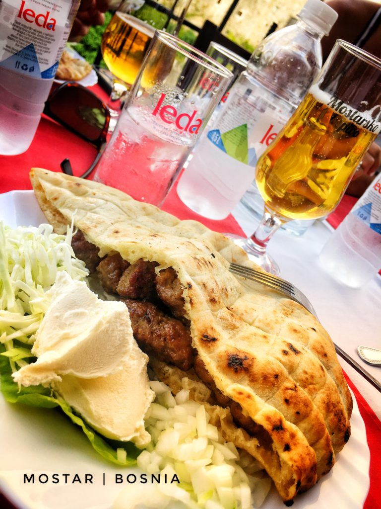 Cevapi is a traditional grilled meat sausage served with onions, bread, and yogurt in Mostar, Bosnia
