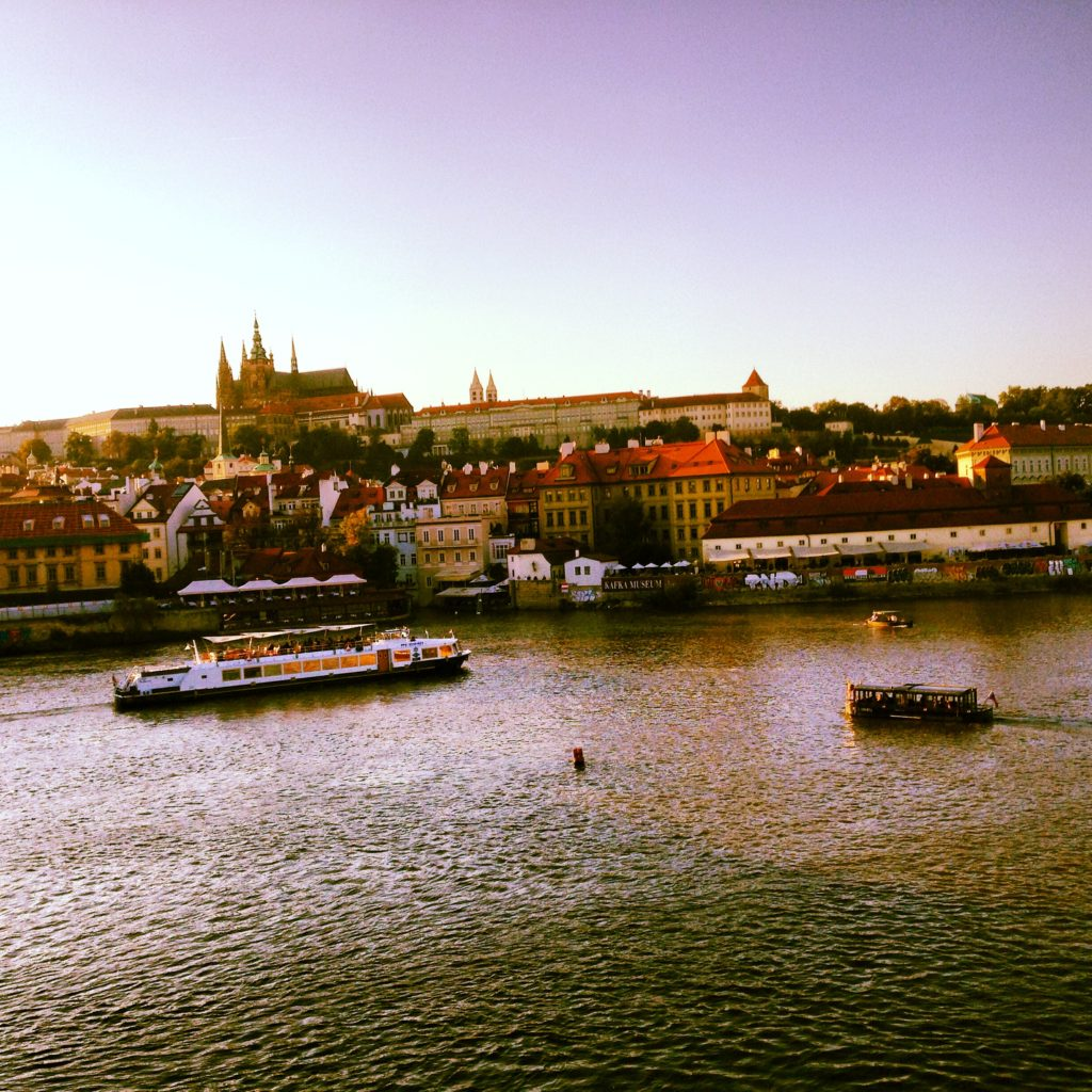 A view of Prague castle and the river at sunset