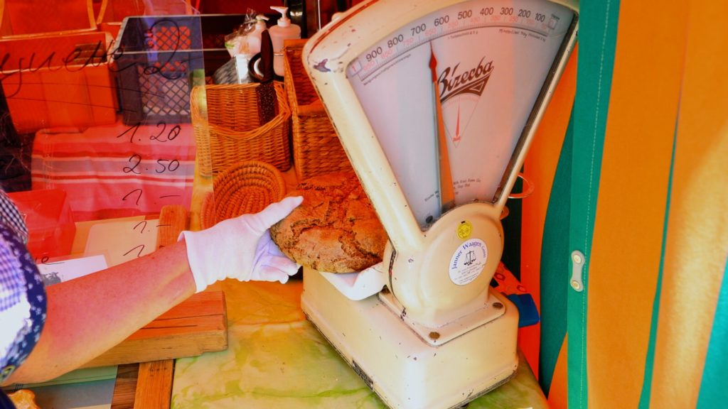 Weiden bread employee weighing a loaf of local bread