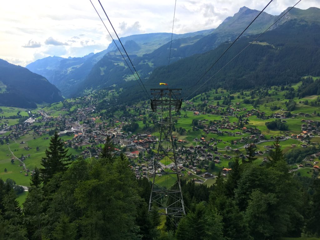 Views of the mountains, trees, and the city of Grindelwald from the Luftseilbahn Grindelwald Pfingstegg