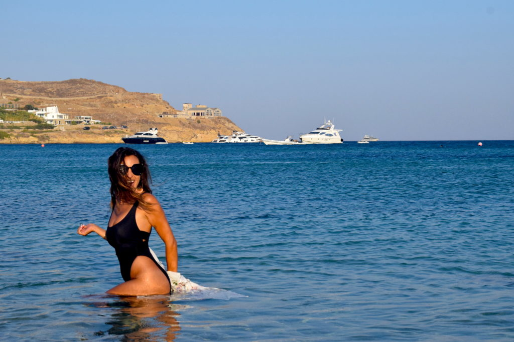 Walking through the warm waters of Lohan beach club in mykonos greece