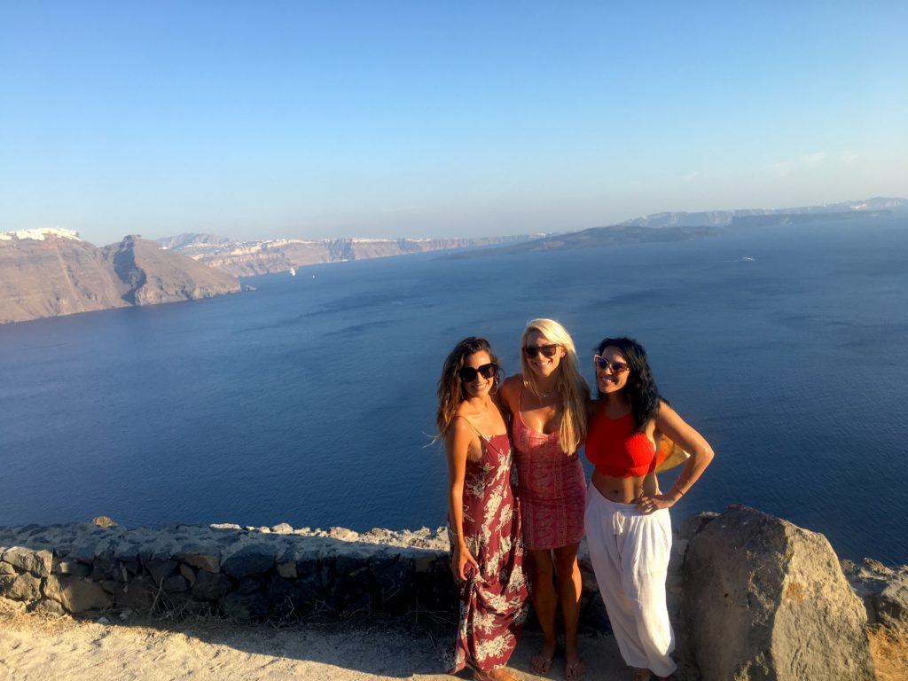Girls posing on the cliffs of Santorini