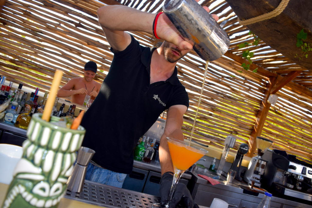 Waiter at Tortuga beach bar pouring a cocktail in Naxos Greece