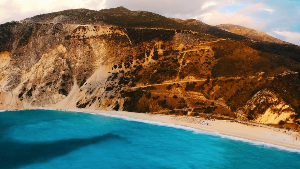 drone picture of mountains and driving route down to myrtos beach