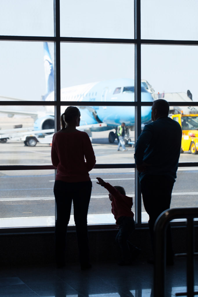 Young family watching planes at an airport standing together in front of a large glass window overlooking a jetliner being readied for takeoff